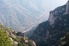 Gelbe Kabine der Gebirgsluftkabelbahn steigt zum Kloster von Montserrat Nebelhafter Gebirgsgebirgsmassiv, -abgrund und -schlucht  Lizenzfreies Stockfoto