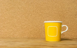 Gelbe Kaffeetasse auf Holztisch Stockfoto