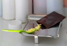Gelbe Kapseln mit Maß löffeln und machen Tasche auf der Zählung des Behälters Reißverschluss zu stockfotografie