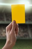 Gelbe Karte mit der Hand vom Referenten, der ein penalt gibt Lizenzfreies Stockfoto