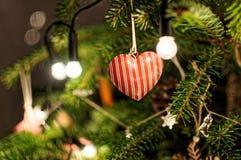 Gelbe Kegel auf weißem Hintergrund Leuchten auf Weihnachtsbaum Herzanhänger auf Weihnachtsbaum Stockbild
