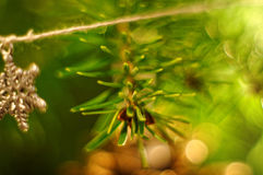 Gelbe Kegel auf weißem Hintergrund Schneeflocke, die an der Schnur hängt Bokeh Hintergrund Weihnachtsbaumzweig Stockbild