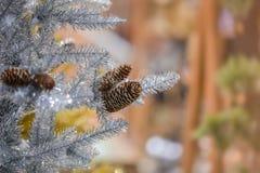 Gelbe Kegel auf weißem Hintergrund Silberner künstlicher Baum mit Kegeln, Hintergrund des neuen Jahres Stockfoto