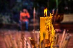 Gelbe Kerze und Weihrauch mit Unschärfehintergrund Stockbilder