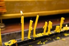 Gelbe Kerzen, die an einem traditionellen thailändischen Buddhisten brennen thailand Lizenzfreies Stockbild