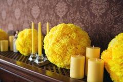 Gelbe Kerzen und ein Ball aus dem Papier, das auf hölzerne Regale, eine Weinleseart der Hausdekoration heraus legt Lizenzfreie Stockfotografie