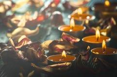 Gelbe Kerzen und plamennoi umgeben durch trockene Blumenblätter von Tulpen Stockbilder