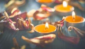 Gelbe Kerzen und plamennoi umgeben durch trockene Blumenblätter von Tulpen Lizenzfreies Stockbild