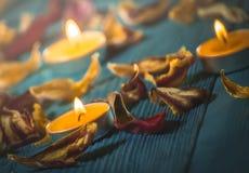 Gelbe Kerzen und plamennoi umgeben durch trockene Blumenblätter von Tulpen Lizenzfreies Stockfoto