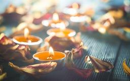 Gelbe Kerzen und plamennoi umgeben durch trockene Blumenblätter von Tulpen Lizenzfreie Stockfotos