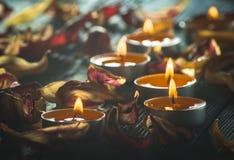 Gelbe Kerzen und plamennoi umgeben durch trockene Blumenblätter von Tulpen Lizenzfreie Stockbilder