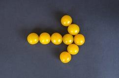 Gelbe Kirschtomaten in einer Form eines Pfeiles auf dunklem Hintergrund Lizenzfreie Stockfotografie