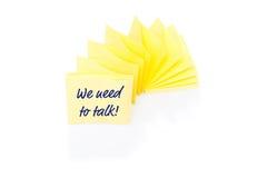 Gelbe klebrige Anmerkung über Block mit Mitteilung, die wir benötigen Lizenzfreies Stockfoto