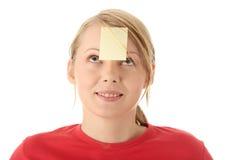Gelbe klebrige Anmerkung über Stirn Stockfotografie