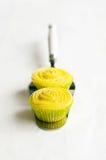 Gelbe kleine Kuchen auf Kuchen schaufeln, weißer Hintergrund stockbilder