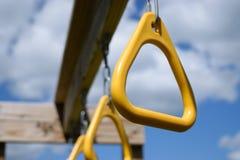 Gelbe Kletterstange-Ringe, die vom Spielplatz-Satz hängen Stockfotografie