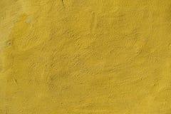 Gelbe konkrete Hintergrundbeschaffenheit mit Schrotten Lizenzfreie Stockfotos