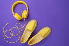 Gelbe Kopfhörer und Sommerschuhe auf purpurrotem Hintergrund Sommermusikkonzept lizenzfreies stockfoto
