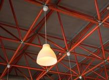 Gelbe Lampe, die von den industriellen roten Deckenbalken hängt stockbild