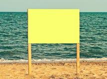 Gelbe leere Anschlagtafel auf sandigem Strand Addieren Sie einfach Ihren Text Stockfotos