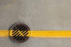 Gelbe Linie über Abflussabdeckung stockfoto