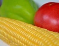 Gelbe Maiskolben, rote Tomate und grüner Paprika liegen auf dem Tisch, Nahaufnahme, Ampelfarben lizenzfreie stockfotografie
