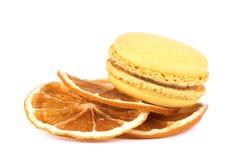 Gelbe Makronen und getrocknete orange Scheiben, lokalisiert auf weißem Hintergrund Lizenzfreies Stockfoto