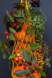 Gelbe Maschentasche, alte Filetarbeit mit neuen organischen gesunden verschiedenen Arten von Kürbisen, dunkler Hintergrund, Hande Stockbilder