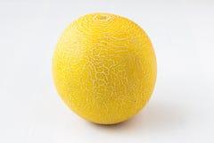 Gelbe Melone auf einem weißen Hintergrund Lizenzfreie Stockfotos