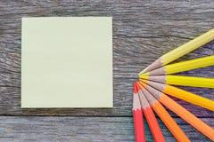Gelbe meno Anmerkung und farbige Bleistifte auf dem hölzernen Hintergrund Lizenzfreie Stockfotografie