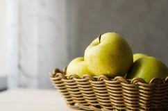 Gelbe nasse frische Äpfel in einem Weidenkorb Stockfotos