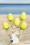 Gelbe Ostereier, hölzernes Kaninchen sind auf dem Strand mit Meer Lizenzfreies Stockfoto