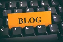 Gelbe Papieranmerkung über schwarze Tastatur mit Schreiben Blog Stockfotografie