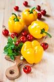 Gelbe Pfeffer, Tomaten und grüner Basilikum auf einem Holztisch Stockfoto