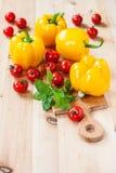 Gelbe Pfeffer, Tomaten und grüner Basilikum auf einem Holztisch Stockbild