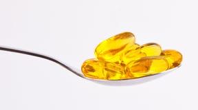 Gelbe Pillen auf Löffel Stockbilder
