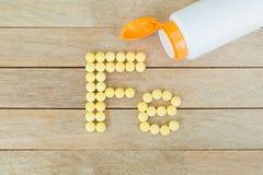 Gelbe Pillen, die Form zu F.E.-Alphabet auf hölzernem Hintergrund bilden Stockfotos