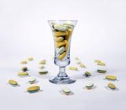 Gelbe Pillen in einem Glas Lizenzfreie Stockbilder