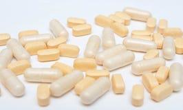Gelbe Pillen oder Kapseln der Medizin auf einer weißen Hintergrundnahaufnahme Vitamine mischen Verordnung von Drogen für Behandlu stockbild