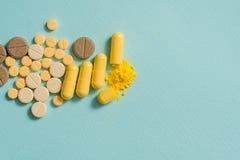 Gelbe Pillen und Kapseln auf einem blauen Hintergrund Öffnen Sie Kapsel, pulverisierte Medizin Stockfoto
