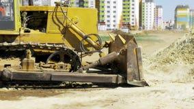 Gelbe Planierraupe in der Bewegung Bau eines Wohnmultiwohnungskomplexes in der Stadt aufbau Video auf Lager stock footage