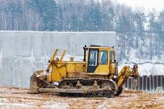Gelbe Planierraupe, die im Winter arbeitet Lizenzfreie Stockbilder
