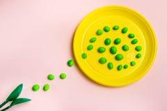Gelbe Plastikplatte mit einem Weg von Bonbons mit grünen Löffeln auf einem rosa Hintergrund stockfoto