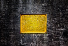 Gelbe Platte auf einer dunklen und düsteren Wand Stockbild