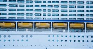 Gelbe Rettungsboote zwischen Balkonen und Öffnungen Stockfotografie