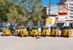 Gelbe Rikscha fährt auf eine Straße in Puttaparthi-Dorf mit einem Taxi Stockfotos