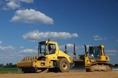 Gelbe Rolle und Planierraupe über blauem Himmel Lizenzfreies Stockfoto