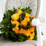 Gelbe Rosen, die auf einem Stuhl liegen Stockbild