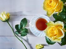 Gelbe Rosen und eine Schale des heißen Getränks lizenzfreies stockbild