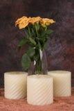 Gelbe Rosen und Kerzen Stockfotografie